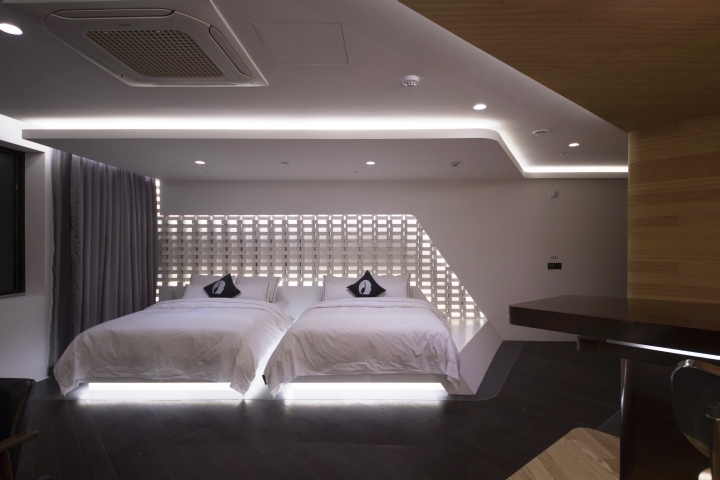 layer of white bricks reflecting ceiling lights adds depth and mystique on the walls along with the walls glistening pale marble bed catches the reflected