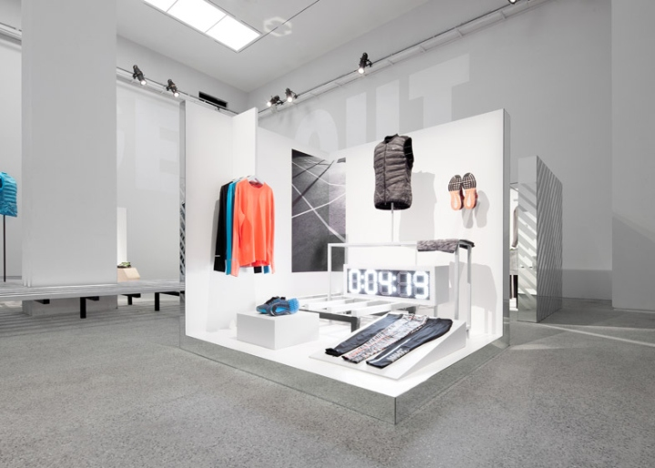 The grid theme is repeated in a second Nike Run Club gym space that  features two rows of running machines encased in cubes formed of singular  neon strips.