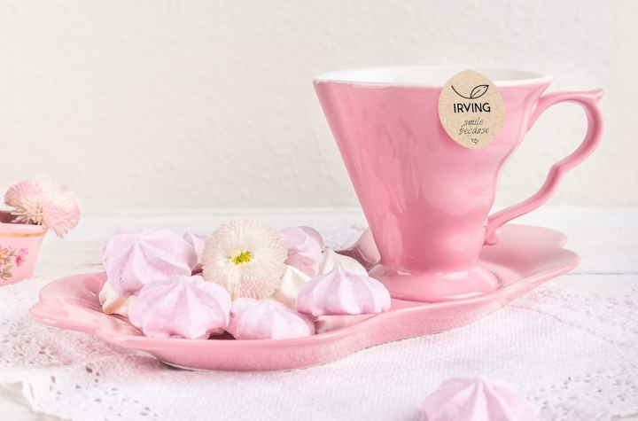 pink tea set with cookies on a white background